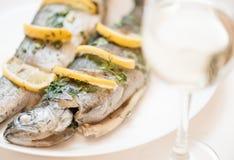Fiskmaträtt på en vit platta med exponeringsglas av vitt vin arkivbild