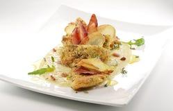 Fiskmaträtten, smaksatte piggvarfiléer täcker med en skorpa, cips, rosti, lagat mat med grädde p Arkivbild