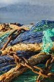 Fisknät med rostiga kedjor med det blåa havet Fotografering för Bildbyråer