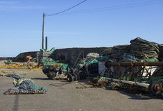 Fisknät och hummerkrukor som ner lagras på kajen och mot hamnväggen på Kilkeel i det nordliga länet - Irland arkivfoto