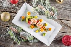 Fiskstartknappmat på den vita plattan med julgarnering produktfotografi och modern gastronomi arkivbild