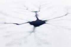 Fissures et trou en glace sur l'étang Photographie stock libre de droits