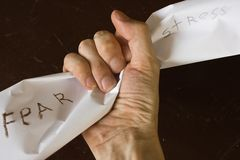 Fist. The hand squeezes a piece of paper against a dark background Royalty Free Stock Photography