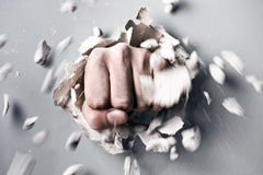 Fist. A wall is broken through by a fist stock photography
