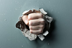 Fist. A wall is broken through by a fist royalty free stock image