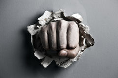 Fist. A wall is broken through by a fist stock photo