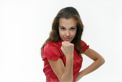 Fist. The woman on a white background in a red blouse shakes a fist Royalty Free Stock Photo