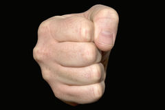 Fist. Close up of a clenched fist on a black background Stock Image