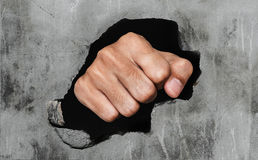 Fist breaking concrete wall stock photo