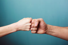 Fist bump. Young men and women are fist bumping stock photos