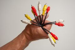 Fist of colorful cords. Hand making a fist around a bunch of different types of red yellow and white cords stock photos