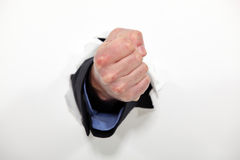 Fist emerging from wall Stock Images