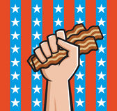 Fist Full of American Bacon. Raised fist holding bacon in front of American stars and stripes Royalty Free Stock Photo