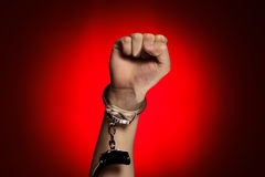 Fist and handcuffs opened over red background Stock Images