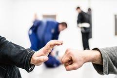 Fist hands bump at the brazilian Jiu Jitsu training. Hand slap and bump at the start of the brazilian jiu jitsu roll training session royalty free stock photo