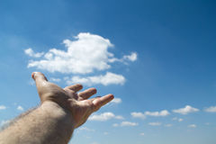 Fist holding a large cloud. Royalty Free Stock Images