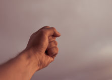 Fist of a man reaching sky. Stock Image