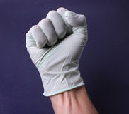 Fist in medical glove Stock Image