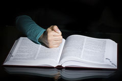 Fist over open book. A female hand in a fist over an open book Stock Images