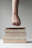 Fist over pile of book Stock Photo
