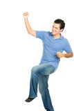 Fist Pumping Hispanic Male No Shoes Celebration. Happy smiling good looking hispanic male in casual clothes, no shoes celebrating indoors with victorious fist Royalty Free Stock Images