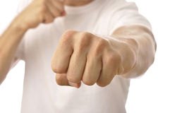 Fist punch. Closeup of fist of unrecognizable man in white T-shirt punching at camera Royalty Free Stock Images