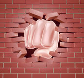 Fist Punching Through Brick Wall Stock Photo