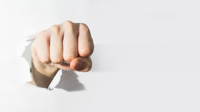 Fist punching through paper, the white paper, The concept of agg Royalty Free Stock Photo