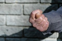 Fist with a thumb between the index and middle fingers, fig sign. Gesture mens hand of negative. Concept of rejection. Closeup. View on gray stone wall stock photo