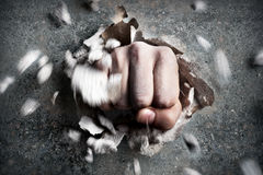 Fist. A wall is broken through by a fist royalty free stock photo