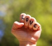 A fist with the word love written or tattooed on the fingers Stock Photo