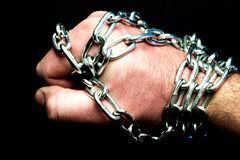 A fisted chain-wrapped leather stiffened from a sprinkle, a metal chain and a hand. A fisted chain-wrapped leather stiffened from a sprinkle Stock Image