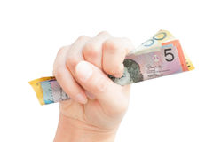 Fistful of Australian cash. One hand clutching Australian money bank notes in a fist,  on white Royalty Free Stock Photos