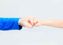 Fists of an adult and a child on white Stock Photo