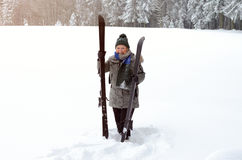 Fit active elderly lady with her skis. Standing in deep fresh snow in a rural winter landscape smiling at the camera, with copy space royalty free stock photos