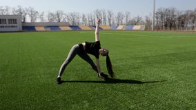 Fit active good looking young woman does leg stretching exercise to warm up muscles working out outside at big stadium stock footage