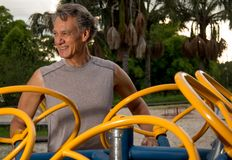 Senior Man Exercising Outdoors. Fit Active Senior Man Exercising on an Tai Chi Spinning Machine at a Outdoors Public Fitness Park Stock Image