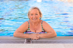 Fit active senior woman enjoying retirement. Standing chest high in the cool inviting water a swimming pool smiling happily at the camera royalty free stock images