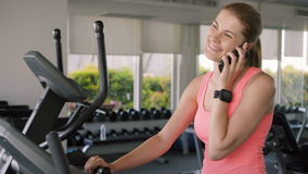 Fit active sportive woman doing exercises on velosimulator. Using her smartphone, talking to friend. Beautiful fit active sportive young woman in pink t-shirt stock footage
