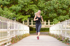 Fit active woman running across a bridge. Approaching the camera with a smile and her hair flying in a fitness and healthy outdoors lifestyle concept Royalty Free Stock Photography