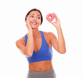Fit adult woman choosing sugary food. Fit adult woman in sport clothing choosing sugary food on isolated background Stock Photo
