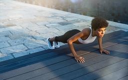 Woman doing push ups outdoor. Fit african girl doing pushup exercise outdoor in the city street at dusk. Brazilian fitness woman working on abdominal muscles and stock photos
