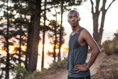 Fit African man standing on a trail while out jogging Royalty Free Stock Photo
