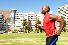 Fit african sportsman running outdoors at city park Royalty Free Stock Images