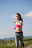Fit and agile. Fit and agile young brunette woman running outdoors in the sunshine stock photos