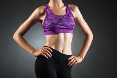 Fit anonymous girl akimbo. Fit anonymous sport-girl akimbo in black yoga pants and purple top. Studio portrait black background Stock Images