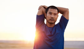 Fit Asian man stretching his shoulders before a morning run. Focused and athletic young Asian man stretching his arms before going for a solo run outside on a Stock Image