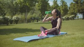 Fit asian woman sipping energy drink on finess mat. Sporty female having energy drink during fitness workout on green park lawn. Young chinese woman sitting on stock video