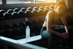 Fit asian woman sitting and relax after the training session in gym,Female taking a break after exercise and workout,Concept healt stock images