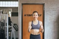 Fit asian woman thumb up and relax after the training session in gym,Concept healthy and lifestyle,Female taking a break after exe stock photos